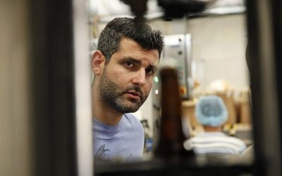 Yazan Karadsheh, founder of the Carakale Brewery in Fuheis, Jordan, watches a machine fill beer bottles and cap them on an assembly line, September 6, 2016 (AP Photo/Sam McNeil).