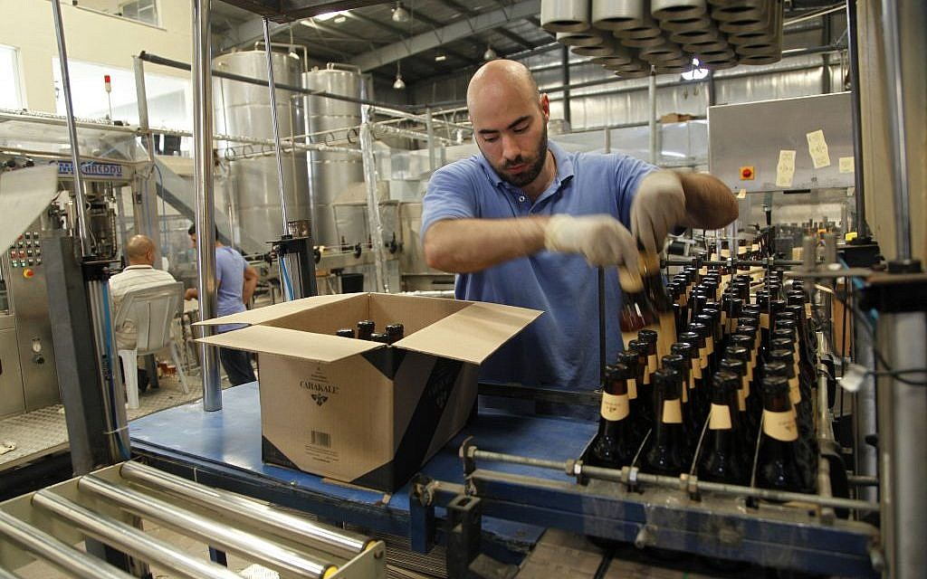 Yazan Karadsheh, right, founder of the Carakale Brewery in Fuheis, Jordan, talks to a technician while head brewer Jordan Wombeke quality tastes beer off the assembly line, September 6, 2016 (AP Photo/Sam McNeil)