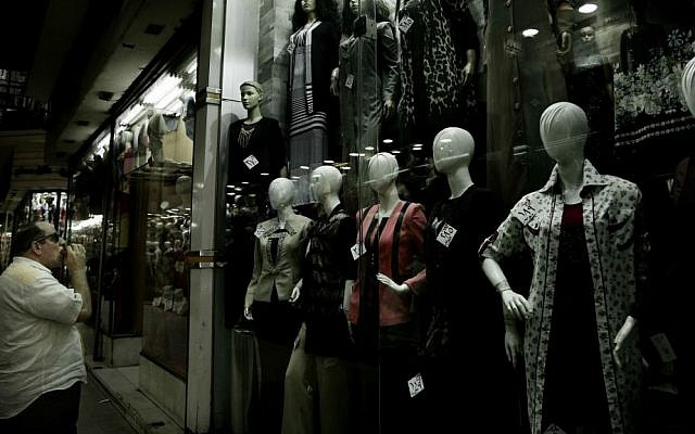 In this Wednesday, Aug. 9, 2016 file photo, a man looks at a women's boutique with discounted prices attached to the clothes in downtown Cairo, Egypt. (AP Photo/Nariman El-Mofty, File)