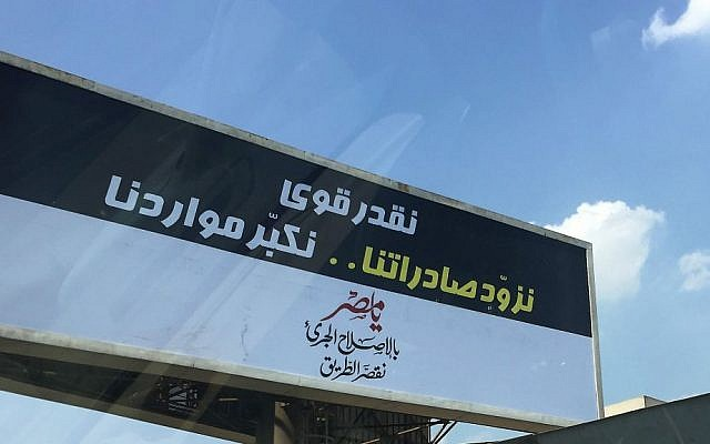 "A motorist drives past a government billboard in Cairo, Saturday, Sept. 3, 2016, which reads in Arabic: ""We sure can...boost our exports and increase our resources. Oh, Egypt, With bold reforms, we shorten the road."" (AP Photo/Hamza Hendawi)"