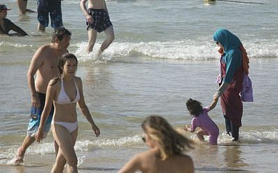 In this Friday, Sept. 2, 2016 photo, a Muslim woman holds her child at a beach in Tel Aviv, Israel. (AP Photo/Ariel Schalit)