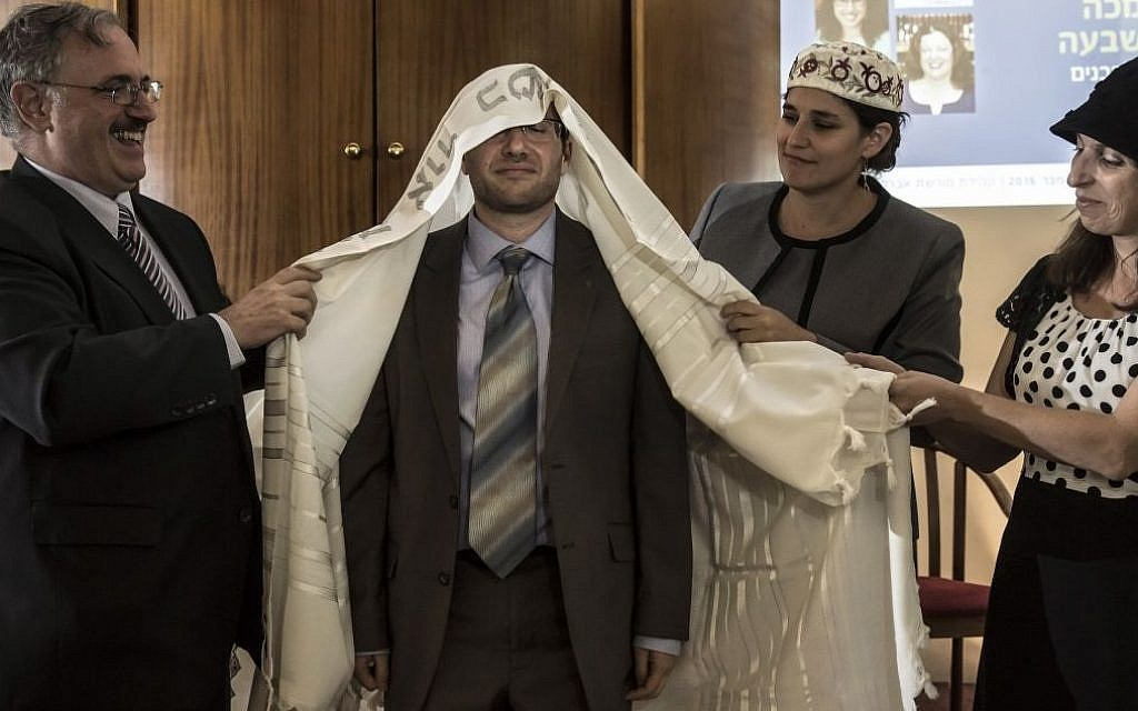 In this Wednesday, Sept. 14, 2016 photo, American-Israeli Arie Hasit, center, is ordained a rabbi at the Schechter Rabbinical Seminary in Jerusalem. (AP/Tsafrir Abayov)