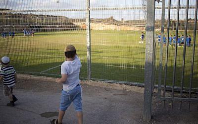 Children watch a soccer training session in the West Bank settlement of Givat Ze'ev, near Jerusalem, Sept. 22, 2016 (AP Photo/Ariel Schalit)