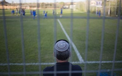 A man watches his son during a training session of the Beitar Shabi Givat Zeev soccer club, in the West Bank Jewish settlement of Givat Ze'ev, near Jerusalem, Thursday, Sept. 22, 2016. (AP Photo/Ariel Schalit)