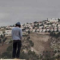 In this Dec. 5, 2012 file photo, a Jewish settler looks at the West Bank settlement of Maaleh Adumim, from the E-1 area on the eastern outskirts of Jerusalem.  (AP Photo/Sebastian Scheiner, File)