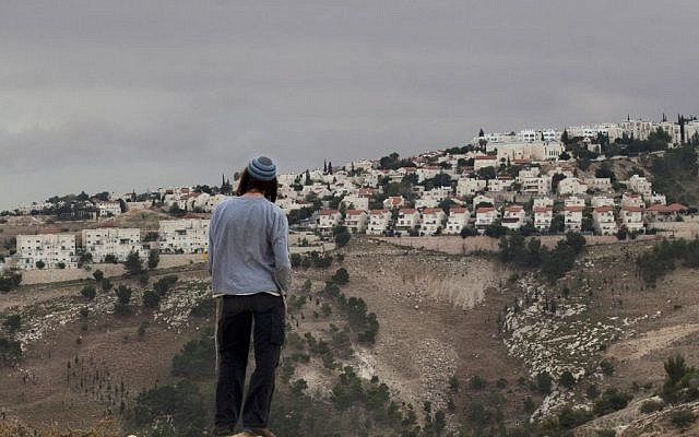 A Jewish settler looks at the West Bank settlement of Ma'ale Adumim, from the E-1 area on the eastern outskirts of Jerusalem, December 5, 2012. (AP Photo/Sebastian Scheiner, File)