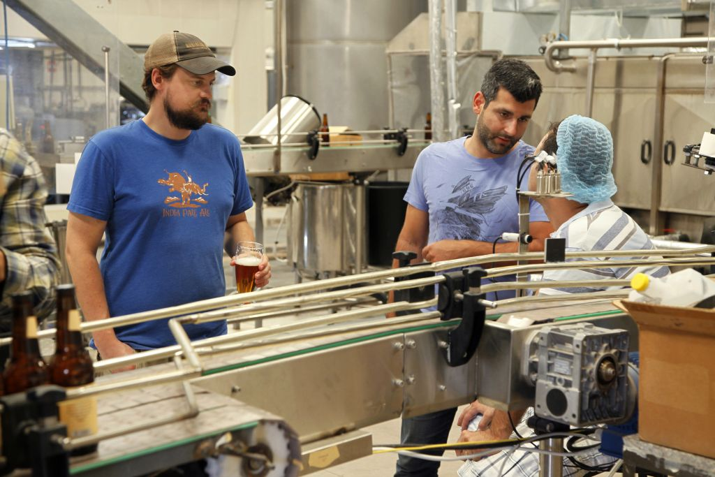 Yazan Karadsheh, right, founder of the Carakale Brewery in Fuheis, Jordan, talks to a technician while head brewer Jordan Wombeke quality tastes beer off the assembly line, September 6, 2016. (AP Photo/Sam McNeil)