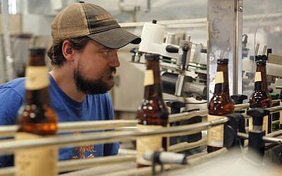 Jordan Wambeke, head brewer of the Carakale Brewery in Fuheis, Jordan, keeps an eye on the labeler machine in the brewery's bottling assembly line, Tuesday, Sept. 6, 2016. (Sam McNeil/AP Photo)