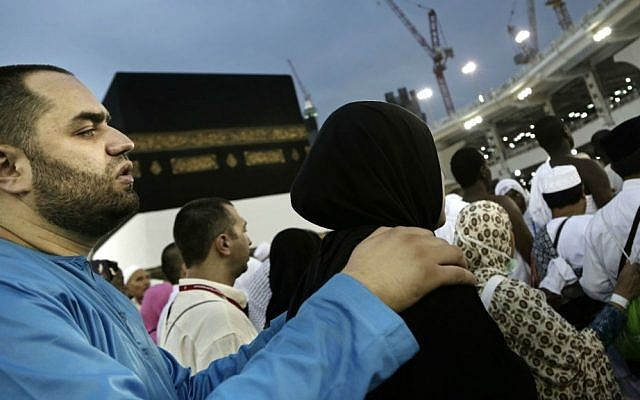 A man holds his wife as they circle the Kaaba, Islam's holiest shrine, at the Grand Mosque in the Muslim holy city of Mecca, Saudi Arabia, Thursday, Sept. 8, 2016. (AP Photo/Nariman El-Mofty)