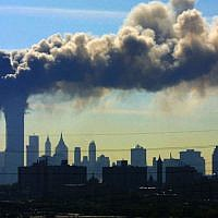 In this Sept. 11, 2001 file photo, as seen from the New Jersey Turnpike near Kearny, New Jersey, smoke billows from the twin towers of the World Trade Center in New York after airplanes flown by Al-Qaeda terrorists crashed into both towers. (AP Photo/Gene Boyars, File)