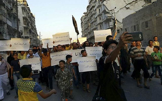 In this Sept. 13, 2016 file photo provided by Modar Shekho, activists in Syria's besieged Aleppo protest against the United Nations for what they say is its failure to lift the siege off their rebel-held area, in Aleppo, Syria. (Modar Shekho via AP, File)