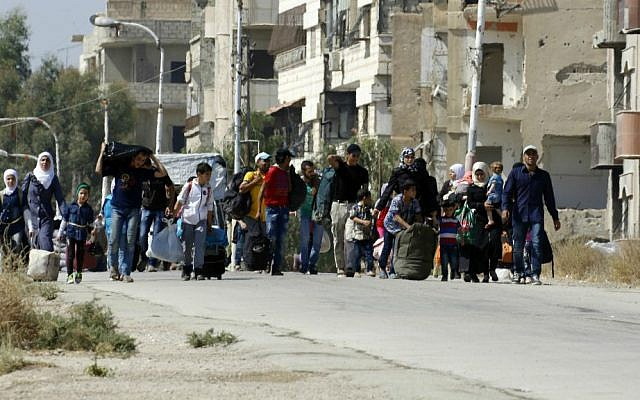 Syrians leave the Moadamiyeh suburb of Damascus, Syria, on Friday, Sept. 2, 2016. (AP Photo)