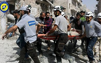 Rescue workers work at the site of airstrikes in the al-Sakhour neighborhood of the rebel-held part of eastern Aleppo, Syria, September 21, 2016. (Syrian Civil Defense White Helmets via AP)