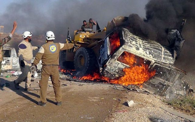 This photo provided by the Syria Press Center (SPC), an anti-government media group, shows rescue workers using a bulldozer to remove a burned van after airstrikes hit west of the town of Suran in Hama province, Syria, Thursday, Sept. 1, 2016, killing a dozen people. (Syria Press Center via AP)