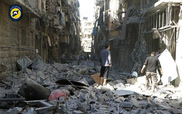Syrians inspect damaged buildings after airstrikes hit in Aleppo, Syria, September 24, 2016. (Syrian Civil Defense White Helmets via AP)