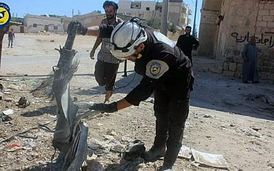 In this photo provided by the Syrian Civil Defense group known as the White Helmets, members of Civil Defense inspect cluster bombs in the Khan Sheikhoun neighborhood of Idlib, Syria, Thursday, Sept. 29, 2016. (Syrian Civil Defense White Helmets via AP)