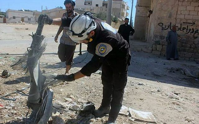 In this photo, members of the Syrian Civil Defense group, known as the White Helmets, inspect cluster bombs in the Khan Sheikhoun neighborhood of Idlib, Syria, September 29, 2016. (Syrian Civil Defense White Helmets via AP)