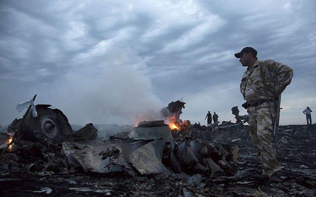 People walk among the debris, at the crash site of a passenger plane near the village of Grabovo, Ukraine, July 17, 2014. (AP/Dmitry Lovetsky, File)