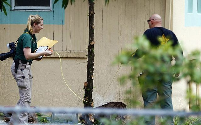 Investigators with the St. Lucie County Sheriff's Office work in a yard Monday, Sept. 12, 2016, at the Fort Pierce Islamic Center in Fort Pierce, Fla., after an apparent arsonist started a fire at the back of the center earlier that morning. (Adam Sacasa/South Florida Sun-Sentinel via AP)