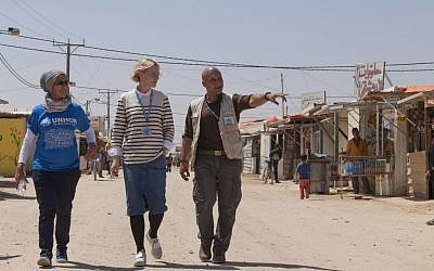 In this undated handout photo released by UNHCR on Monday, Sept 12 2016, UNHCR goodwill ambassador Cate Blanchett, center, and camp manager Hovig Etyemezian, right, walk at Zaatari refugee camp as they visit Syrian refugees in Jordan. (Jordi Matas/UNHCR via AP)