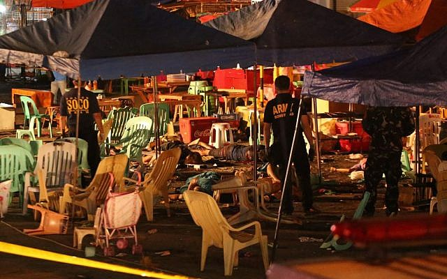 Philippine police officers stand beside bodies of victims after an explosion at a night market that has left about 14 people dead and wounded several others in southern Davao city, Philippines late Friday Sept. 2, 2016 (AP/Manman Dejeto)