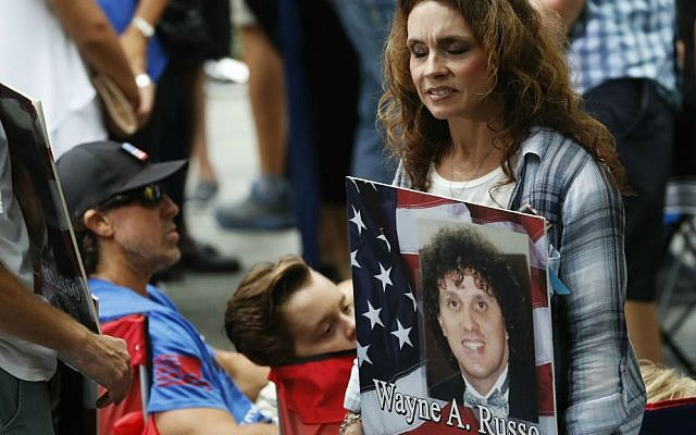 A mourner holds a photo of her loved one during the 15th anniversary of the attacks on the World Trade Center at the National September 11 Memorial, Sunday, Sept. 11, 2016, in New York. (AP Photo/Mary Altaffer)