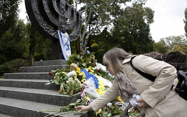 A woman lays a stone to Menorah monument in Babi Yar ravine where Nazi troops machine-gunned tens of thousands of Jews during WWII, Kiev, Ukraine, September 29, 2016. (AP/Sergei Chuzavkov)