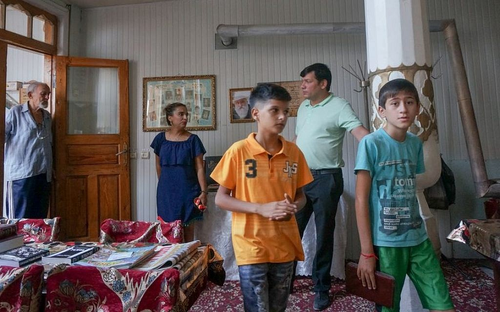 Shirin Yakubov visiting the main synagogue of Bukhara, Uzbekistan, with her son, in orange shirt, his friend and the site's two Muslim caretakers, September 9, 2016. (Cnaan Liphshiz/JTA)