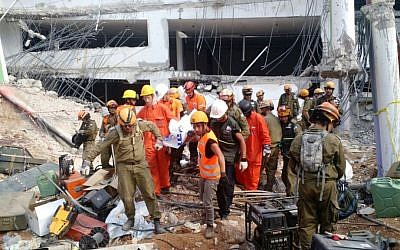 Search and rescue workers remove a fourth body from the rubble of a collapsed parking garage in Tel Aviv on September 6, 2016. (Judah Ari Gross/Times of Israel)
