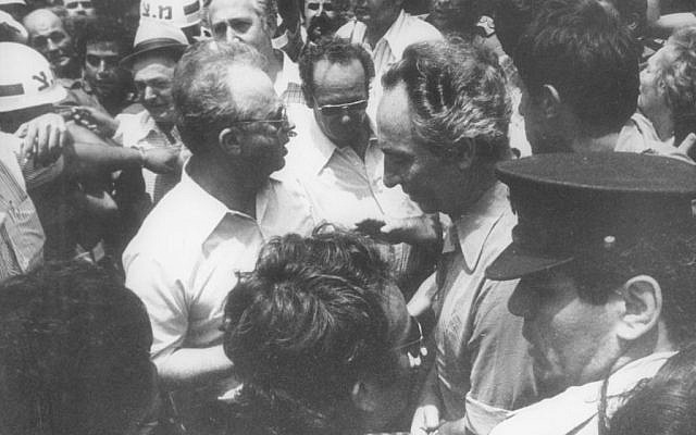 Defense Minister Shimon Peres (r) with Prime Minster Yitzhak Rabin welcoming the released Entebbe hostages upon their return to Israel on July 4, 1976. (Defense Ministry Archives)