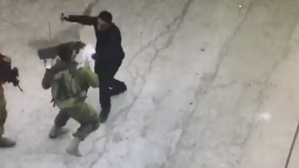 Palestinian assailant Hatem Abdel-Hafiz al-Shaloudi attacks Israeli soldiers with a knife in Hebron on September 17, 2016 (screen capture)