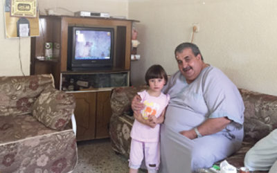 The patriarch of the Kirresh  family , Mazen,  sitting with his granddaughter in their home. The Kirresh family was evicted September 15th by Israeli authorities after losing a battle in Israeli courts to remain tenants.  (courtesy OCHA)
