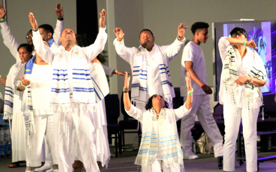 Bishop Wayne Jackson of Great Faith Ministries in Detroit leads members of his church in prayer while wearing traditional Jewish prayer shawls (Courtesy)