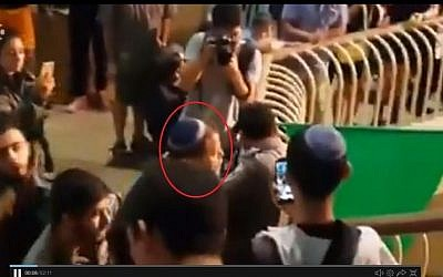 Lehava leader Bentzi Gopstein (circled in red) arguing with a police officer at a choir performance in Jerusalem on September 22 2016. (screen capture: Channel 10)