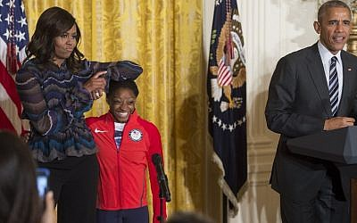 First Lady Michelle Obama jokingly rests her arm on US Olympic gymnast Simone Biles alongside President Barack Obama (R) at a ceremony honoring US Olympians in the East Room of the White House in Washington, DC, September 29, 2016. (AFP PHOTO / SAUL LOEB)