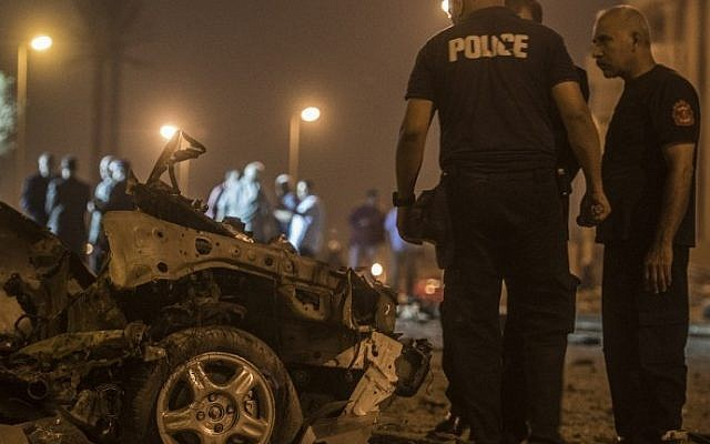 Egyptian policemen inspect the wreckage of a car bomb that exploded in a Cairo suburb after Egypt's deputy prosecutor general drove by late on September 29, 2016, wounding a passerby. (AFP/Khaled Desouki)