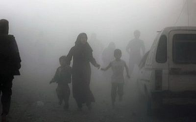 Syrians emerge from a dust cloud following a reported airstrike on Kafr Batna, in the rebel-held Eastern Ghouta area, on the outskirts of the capital Damascus, on September 30, 2016. (AFP/Amer Almohibany)