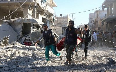 Syrian volunteers carry an injured person on a stretcher following Syrian government airstrikes on the rebel-held neighborhood of Heluk in Aleppo, on September 30, 2016. (AFP PHOTO/THAER MOHAMMED)