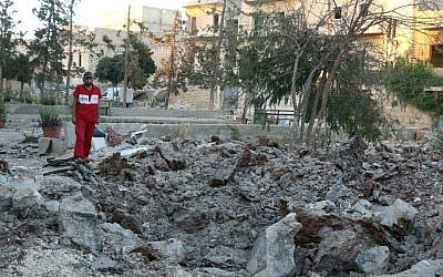 A Syrian medical staff member inspects the damage at the site of a medical facility after it was reportedly hit by Syrian regime barrel bombs on October 1, 2016, in the rebel-held neighborhood of al-Sakhour, in the northern city of Aleppo. (AFP PHOTO / THAER MOHAMMED)