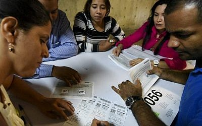 Electoral officials count votes at a polling station after a referendum on whether to ratify a historic peace accord to end Colombia's 52-year war between the state and the communist FARC rebels, in Cali, Colombia, on October 2, 2016. (AFP PHOTO / LUIS ROBAYO)