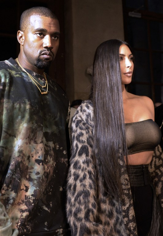 This photo taken on September 29, 2016 shows Kanye West and Kim Kardashian attending the Off-white 2017 spring/summer ready-to-wear collection fashion show in Paris. (AFP PHOTO / ALAIN JOCARD)