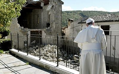 Pope Francis prays in front of damaged houses during his visit to the Italian hamlet of Accumoli on October 4, 2016, after an earthquake hit the area on August 24, claiming nearly 300 lives.  (AFP PHOTO/TIZIANA FABI)