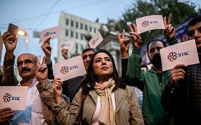 Employees and supporters of pro-Kurdish television channel IMC TV and supporters of other media previously closed by authorities hold signs bear the IMC logo during a demonstration in Istanbul on October 4, 2016. (AFP/Ozan Kose)