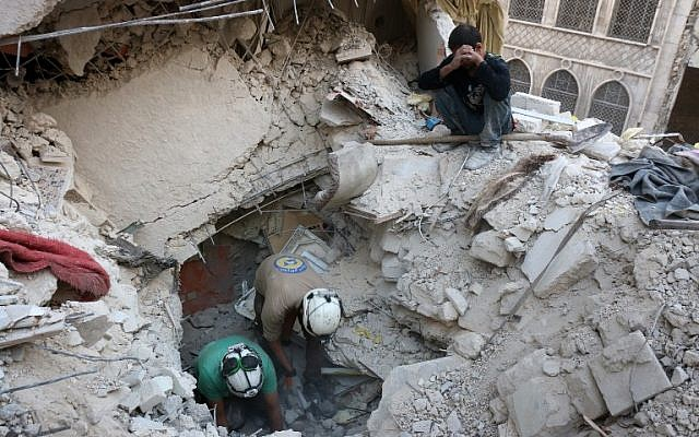 Syrian civil defence volunteers, known as the White Helmets, search for victims amid the rubble of destroyed buildings following a government forces air strike on the rebel-held neighbourhood of Bustan al-Basha in the northern city of Aleppo, on October 4, 2016. (AFP/Thaer Mohammed)