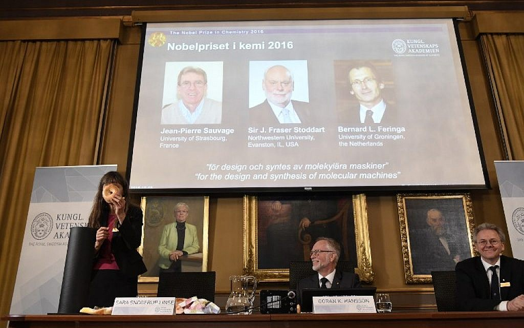 Professor of Physical Chemistry and Chairman of the Nobel Committee for Chemistry, Sara Snogerup Linse, left, uses a bagel to visualize her explanations during a press conference at the Royal Swedish Academy of Sciences in Stockholm on October 5, 2016. The winners of the 2016 Nobel Chemistry Prize, pictured behind her, are Jean-Pierre Sauvage, J Fraser Stoddart and Bernard L Feringa. (AFP / JONATHAN NACKSTRAND)