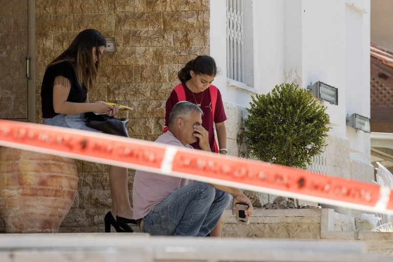 Israelis sit outside their home near the site where a rocket fired from the Gaza Strip hit in the southern Israeli town of Sderot, on October 5, 2016. (Jack Guez/AFP)