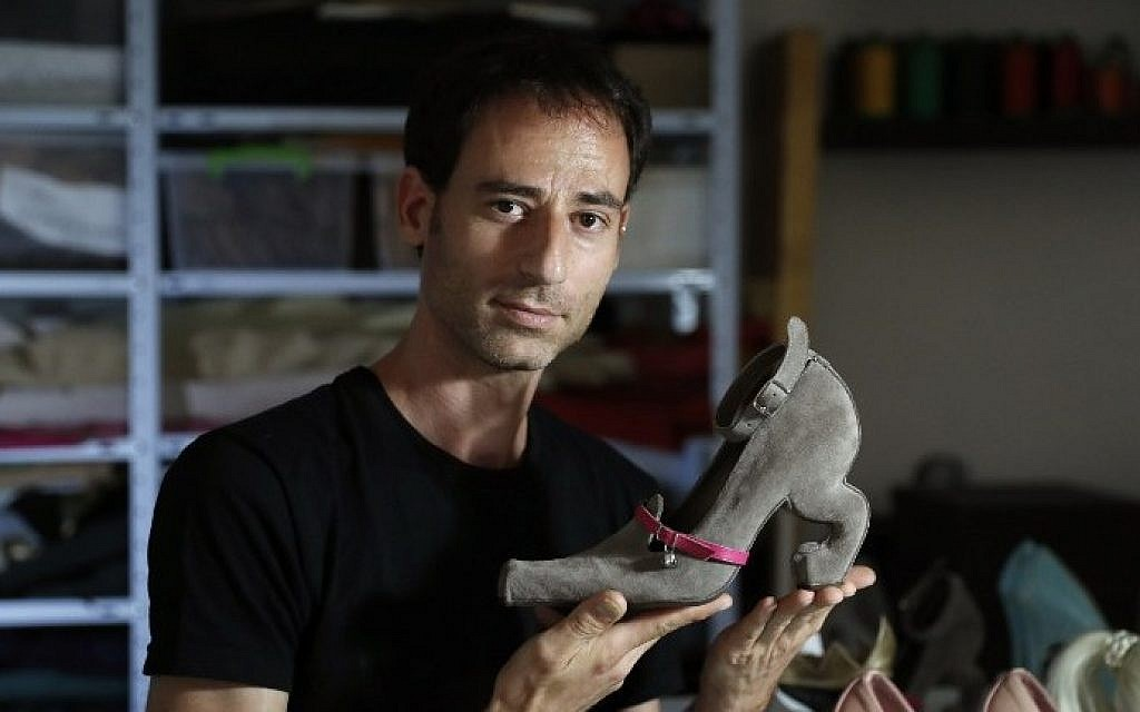 """Israeli shoe designer Kobi Levi poses in his workshop with one of his shoe creations called """"Miao"""" in Tel Aviv, on October 5, 2016. (AFP PHOTO / THOMAS COEX)"""