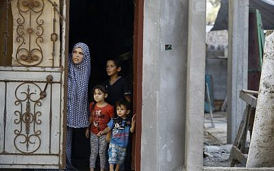 A Palestinian family look out from the doorway of their home in Gaza City's eastern Shujaiya neighborhood following an Israeli military strike on October 5, 2016. (AFP/MOHAMMED ABED)