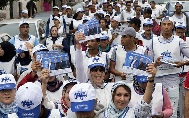 Supporters of Morocco's Party of Authenticity and Modernity (PAM) pass out campaign leaflets in the Moroccan capital , Rabat on October 5, 2016, ahead of the parliamentary election. (AFP/Fadel Senna)