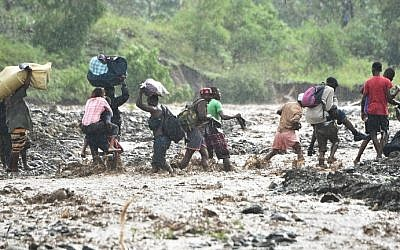 Haitian people cross the river La Digue in Petit Goave where the bridge collapsed during the rains of the Hurricane Matthew, southwest of Port-au-Prince, October 5, 2016. (AFP PHOTO / HECTOR RETAMAL)